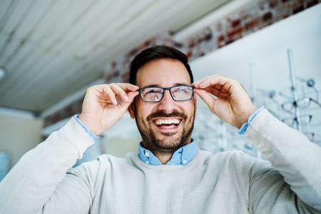 Photo pour Man is choosing glasses in optics store.  - image libre de droit