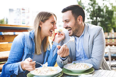 Photo pour Happy couple is enjoying pasta in restaurant. - image libre de droit