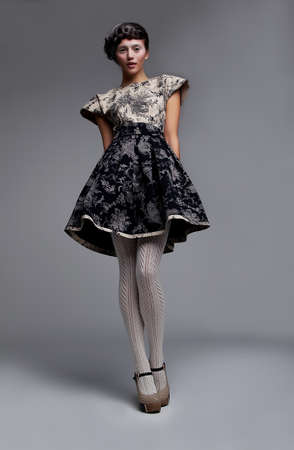 Supermodel fashionable brunette standing in grey  dress