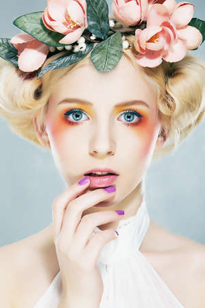 Beautiful blonde supermodel  in wreath of flowers closeup portrait