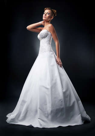 Pretty young fiancee blonde posing in nuptial white dress
