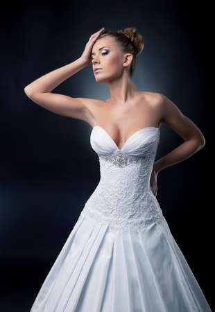 Tempting bride blonde fashion model posing in studio.