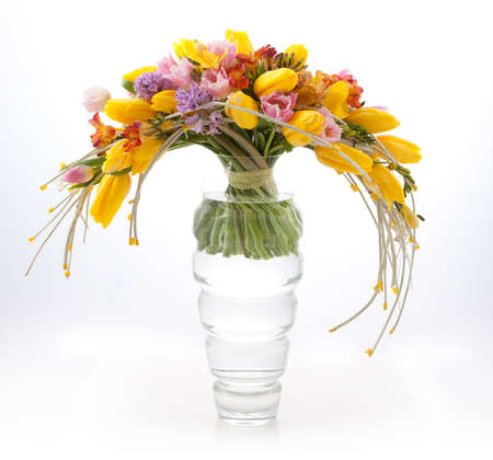 Floristics - colorful vernal flowers bouquet arrangement in vase isolated on white