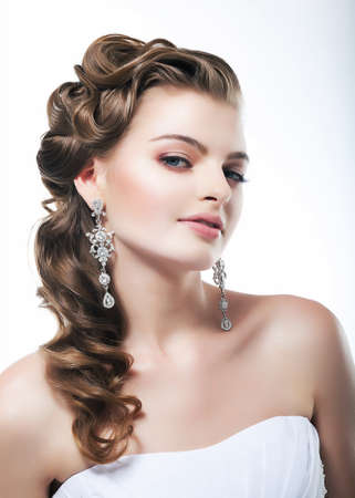 Beautiful bride in white dress  Festive coiffure and makeup