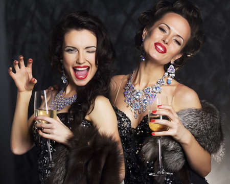 Young women in black elegant dress holding goblets with wine - nightlife