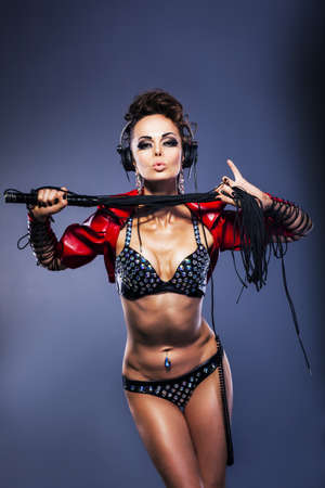 Sexy fetish woman dj  in lingerie holding whip with headphones listening to the music