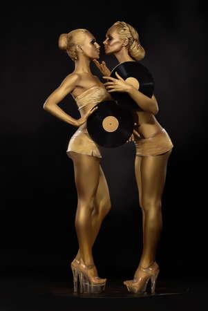 Photo pour Futurism  Creativity  Glossy Gloden Women with Vinyl Record over Black  Shiny Gilded Bodyart - image libre de droit