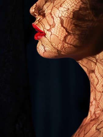 Photo pour Profile of Futuristic Woman s Face with Openwork Lace in Shadows - image libre de droit