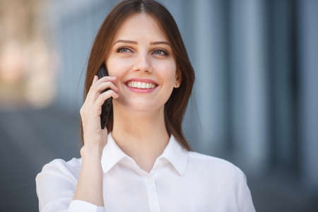 Photo pour Smiling young girl talking on the mobile phone - image libre de droit
