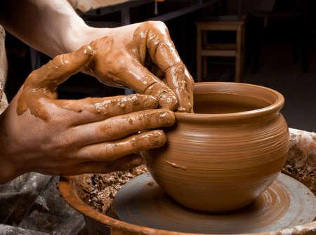 Photo pour hands of a potter, creating an earthen jar on the circle - image libre de droit