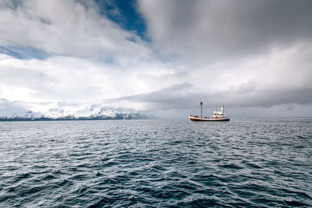 Boat in ocean with cloudy sky. Iceland.