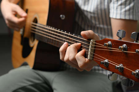 Photo for Man playing acoustic guitar, cover for online courses, learning at home. - Royalty Free Image