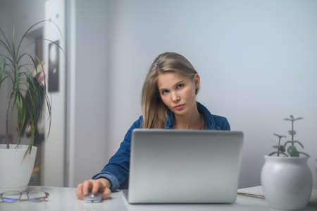 Photo pour A girl with a laptop is studying at an online school. White room background - image libre de droit