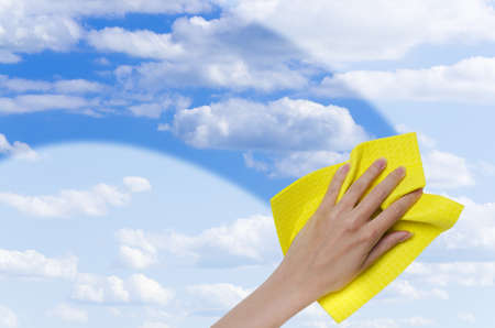Photo pour hand cleaning window making it easier to see blue sky through it - image libre de droit