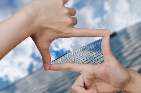 Photo for out of focus business building and fingers creating a square making the vision clear - Royalty Free Image