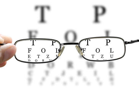 out of focus eye test and a hand holding glasses correcting the vision horizontal