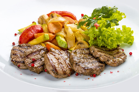 Photo pour Medallions of veal with vegetables and salad. On a white plate - image libre de droit