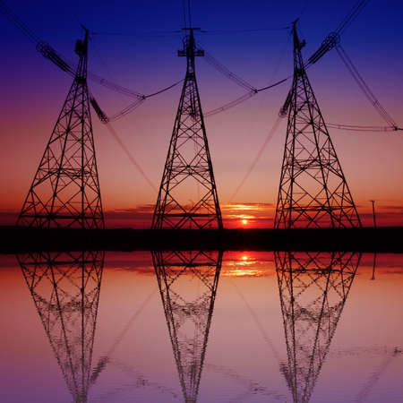 metal electricity pylon transmit electricity reflected in the water, on a background of red sunset