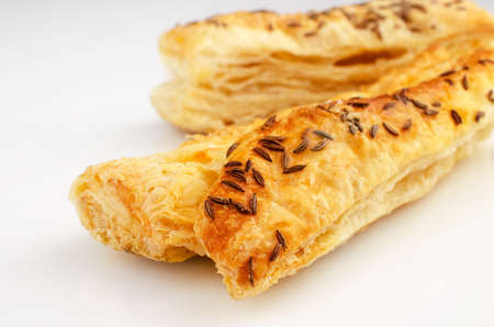 Confectionery theme. Puff pastry, topped with caraway seeds, on white surface.