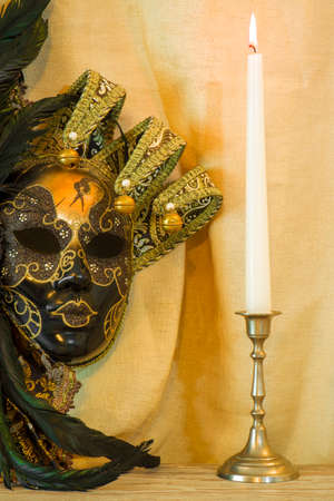 A candle in a candlestick near the Venetian mask on a background of a light cloth
