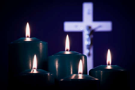 Photo for Lit candles on a white cross, on a blue background - Royalty Free Image