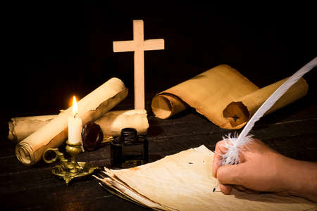 Photo for A hand writing with a pen on the background of papyrus scrolls, against the background of a candle and a cross, against a dark background - Royalty Free Image