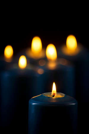 Photo for Lit blue candles isolated on a black background - Royalty Free Image