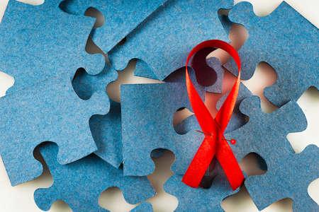 Foto de A red ribbon against a blue puzzle - Imagen libre de derechos
