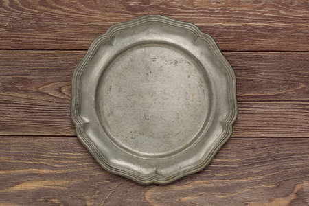 Old tin plate on a wooden countertop