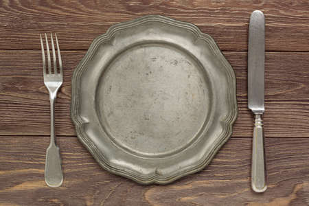 Old tin plate and cutlery on a wooden countertop