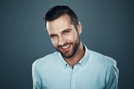 Photo pour He got candid smile. Handsome young man looking at camera and smiling while standing against grey background - image libre de droit