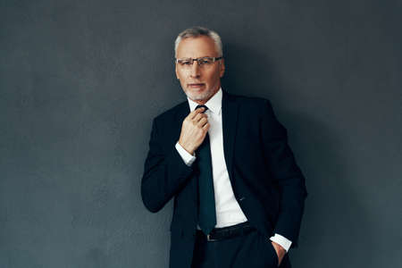 Photo pour Handsome senior man in full suit looking at camera and adjusting tie while standing against grey background - image libre de droit