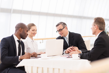 Photo for Business meeting. Business people in formalwear discussing something while sitting together at the table - Royalty Free Image