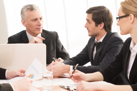 Photo for Business people at the meeting. Four business people in formalwear communicating while sitting together at the meeting - Royalty Free Image