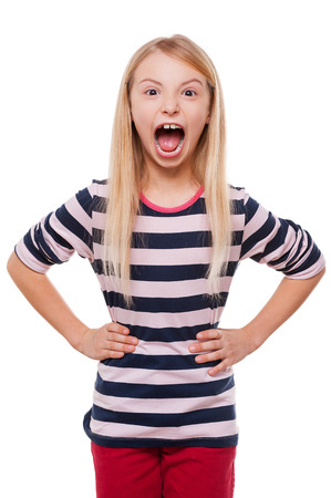 Furious little girl. Angry little girl shouting and holding hands on hip while standing isolated on white