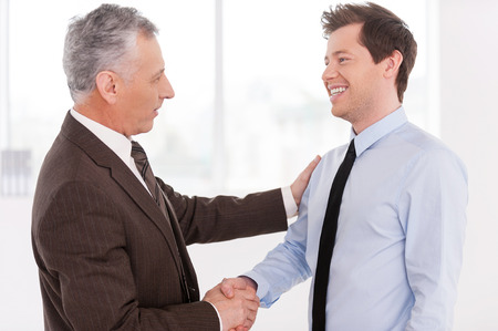 Business partners. Two cheerful business men shaking hands and looking at each otherの写真素材