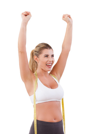 Worked off the excess weight. Happy young woman with measuring tape on her shoulders raising hands up and smiling while standing isolated on white
