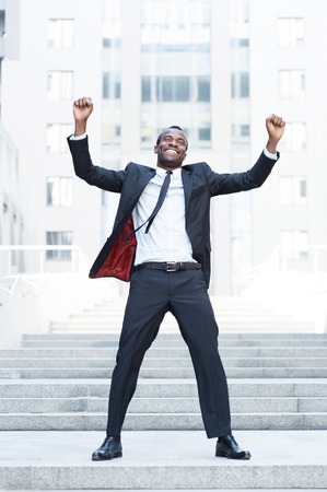 The best day ever! Full length of happy young African man in formalwear keeping arms raised and expressing positivity while standing outdoors