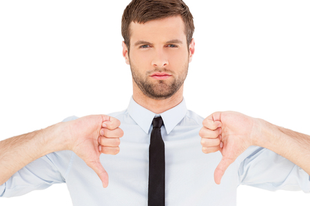 Rejected! Portrait of confident young man in shirt and tie looking at camera and showing his thumbs down while standing isolated on white background