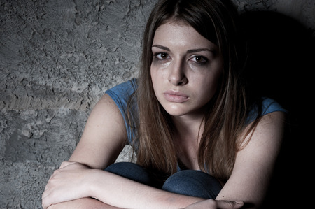 Hopelessness  Top view of young woman crying and looking at camera while sitting against dark wall
