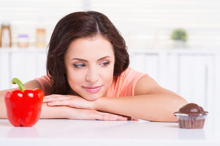 Sweet temptation. Thoughtful young woman choosing what to eat while leaning at the kitchen table with chocolate muffin and fresh pepper laying on it