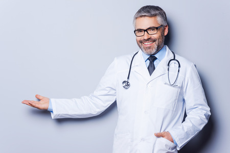 Doctor advertising your product. Cheerful mature doctor looking at camera and pointing away while standing against grey background