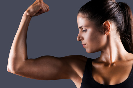 Perfect bicep. Beautiful young sporty woman examining her bicep while standing against grey