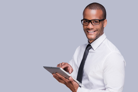 Businessman with digital tablet. Confident young African man in shirt and tie working on digital tablet and smiling while standing against grey background