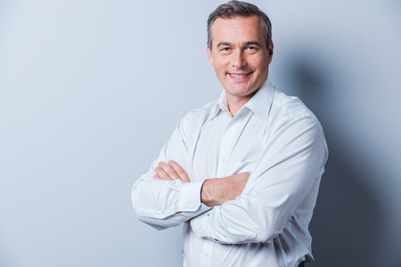 Photo pour Confident mature man. Portrait of confident mature man in shirt looking at camera and smiling while keeping arms crossed and standing against grey background - image libre de droit