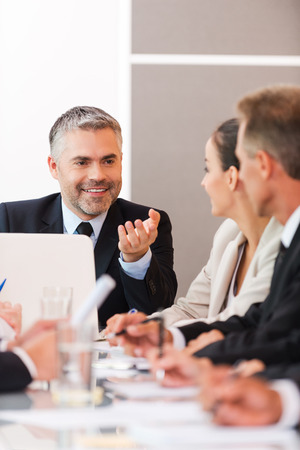 Photo for Good news for our company! Business people in formalwear discussing something while sitting together at the table - Royalty Free Image
