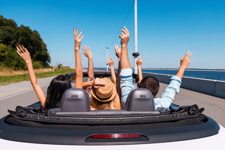 Photo pour Just fun and road ahead. Rear view of young happy people enjoying road trip in their convertible and raising their arms up - image libre de droit