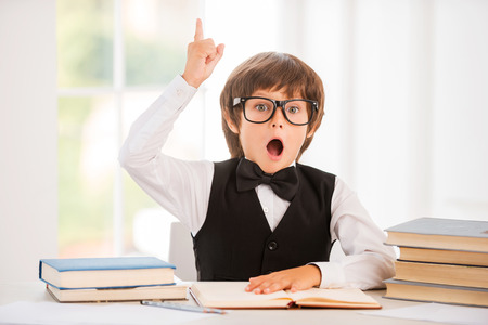Photo pour Bingo! Happy little boy holding book and gesturing while sitting at the table - image libre de droit