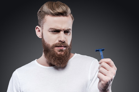 This will not work. Frustrated young bearded man holding razor and looking at it with uncertainty while standing against grey background