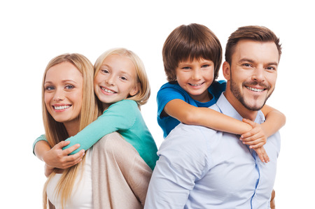 Happy to be a family. Happy family of four bonding to each other and smiling while standing against white